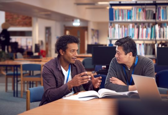 two male adult students talking at table in library