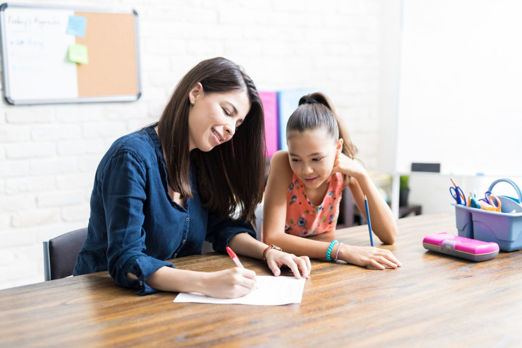 mother working on paper with daughter at table