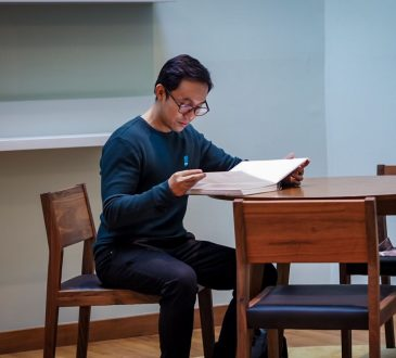 man sitting at table looking through papers