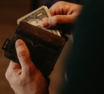 hand pulling bills out of wallet