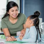 female teaching working with young student