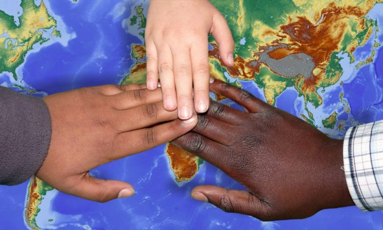 hands of different skin colours over a map