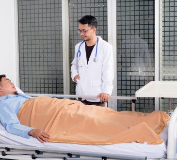 doctor standing beside patient's bed