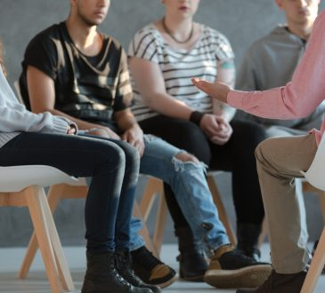 people sitting in chairs for group counselling session