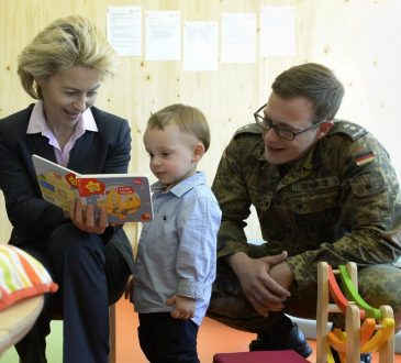 woman reading to small child while soldier looks on