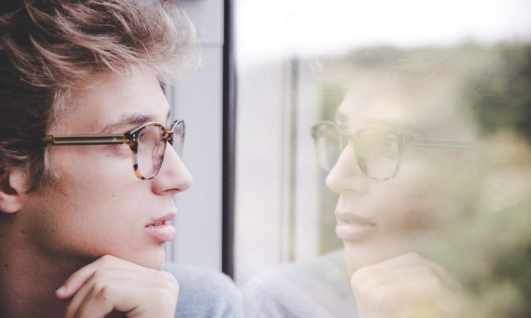 man looking at reflection in window