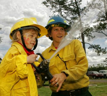 child with firefighter holding hose and spraying water