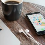 Phone on table beside laptop and coffee mug