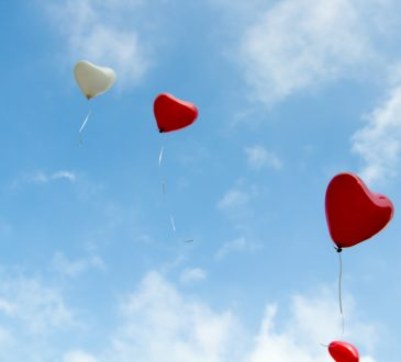 heart-shaped balloons floating in the sky