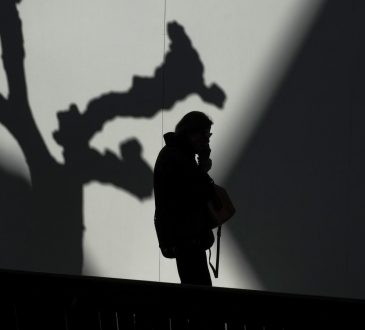 silhouette of man with face in hands