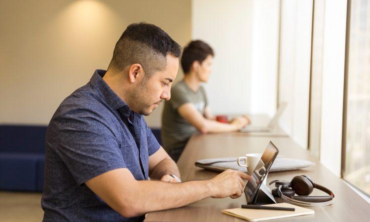 man using tablet at desk