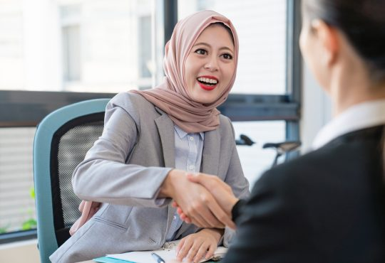 women shake hands at job interview