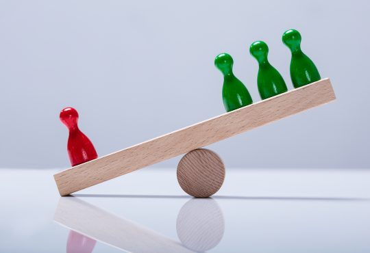 Red And Green Pawns Figures Balancing On Wooden Seesaw