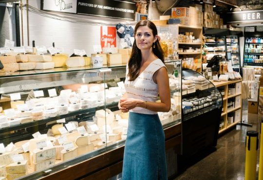woman standing in front of cheese counter in market