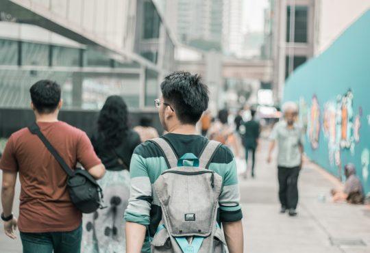 student walking in crowd wearing backpack