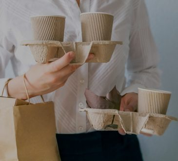 woman holding multiple takeout coffees