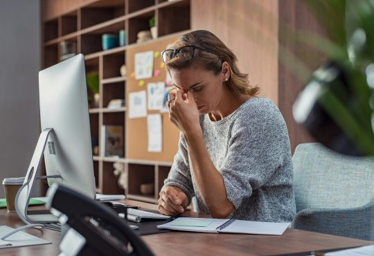woman working at computer with headache