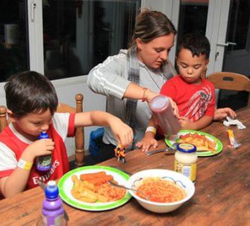 mom feeding children dinner