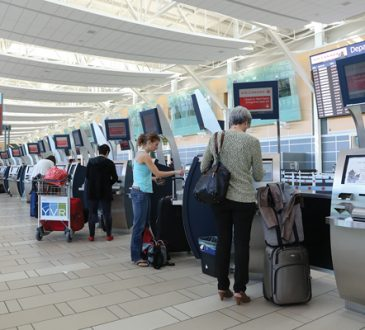 people standing at check-in machines at airport