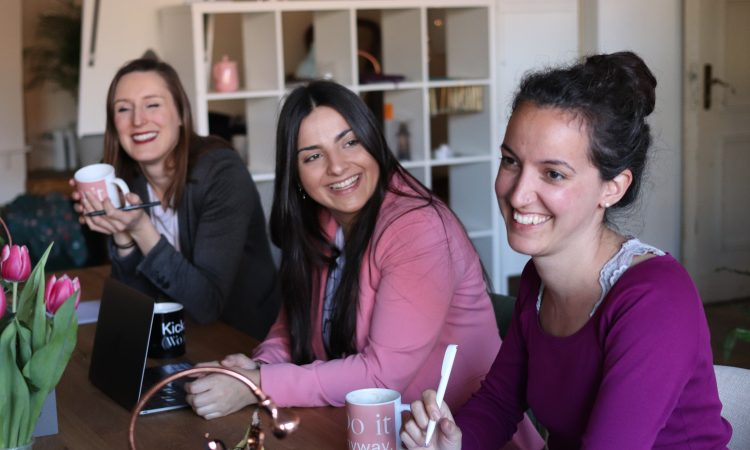 three women sitting at table smiling