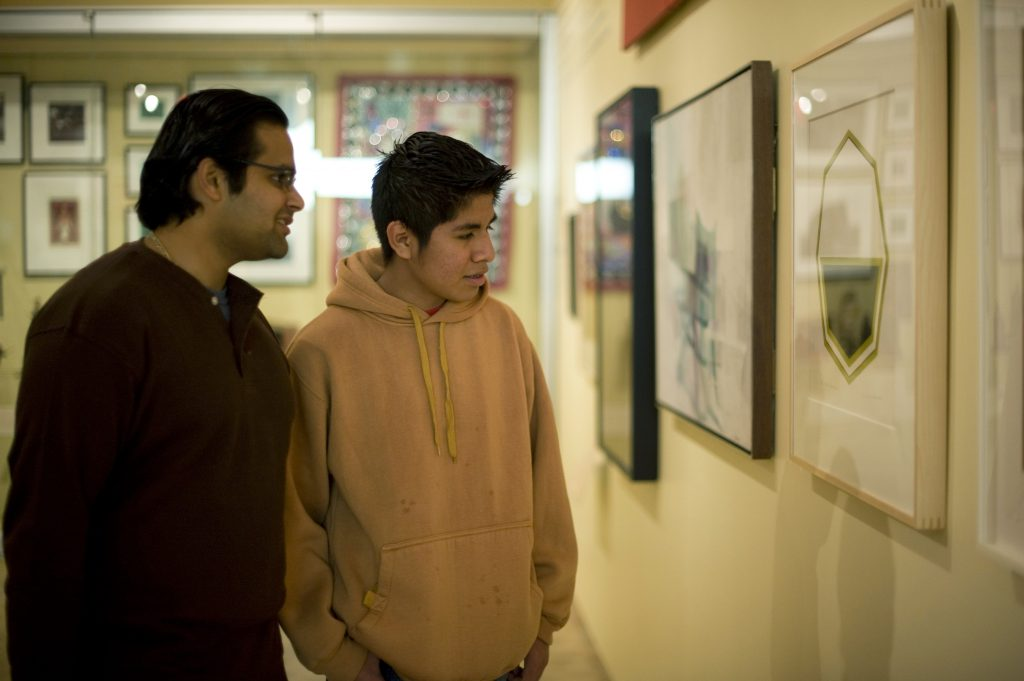 Male mentor and mentee looking at art in museum