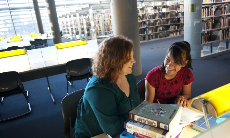 female mentor and mentee sitting together in library