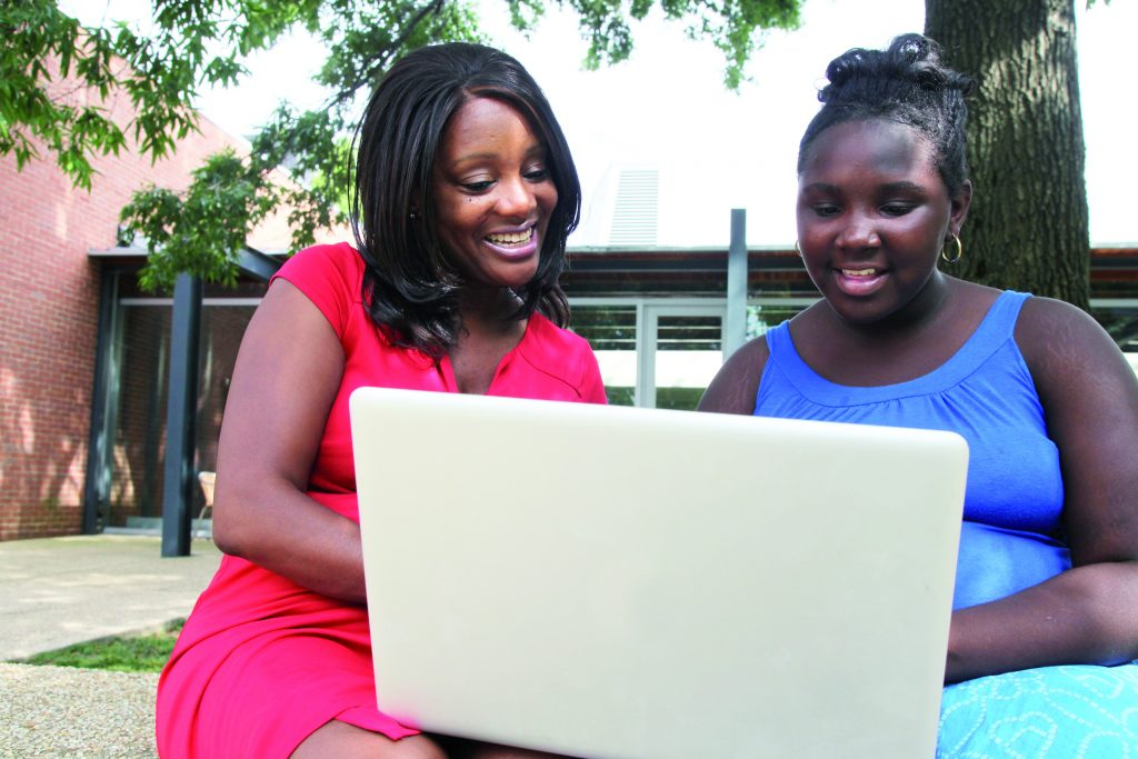 Two women looking at computer screen together