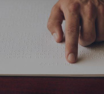 close up of hand of person reading braille