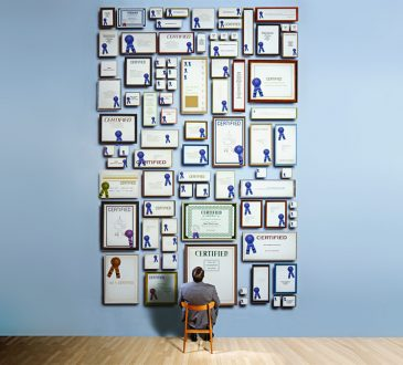 man looking up at wall of framed degrees