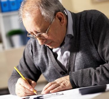 older man sitting and writing