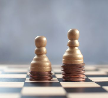 Two chess pawns on top of a heap of coins