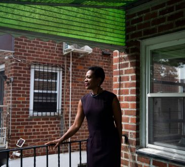 businesswoman standing on porch of house