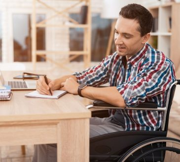 Man sits in a wheelchair at his desk.