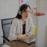 woman wearing headphones while working at desk