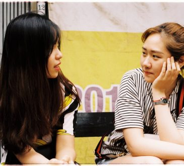 two teen girls sitting and talking