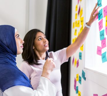 woman in hijab with woman not in hijab putting sticky notes on whiteboard