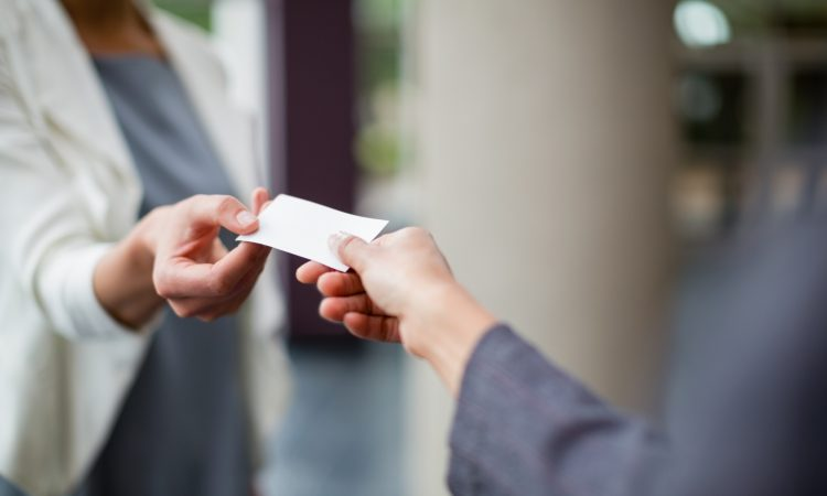 Close-up of business executives exchanging business card at conference centre