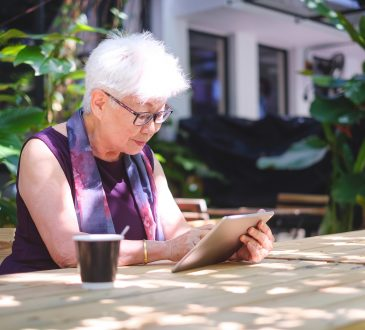 older woman using tablet at cafe