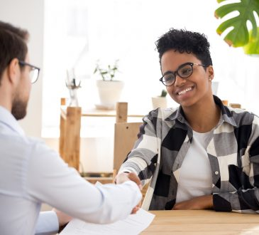 woman and man shaking hands during job interview