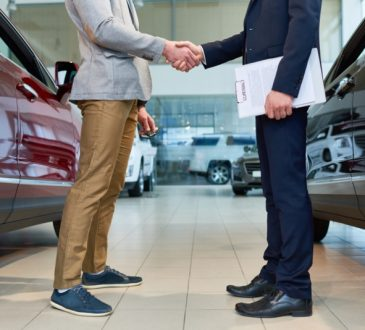 two men shaking hands in car dealership