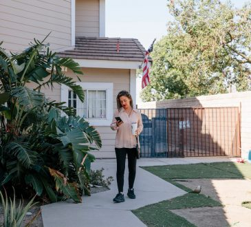 woman looking at phone outside of home