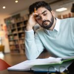 Exhausted young man student studying in a college library