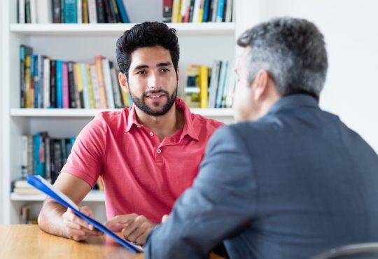 two men talking in office