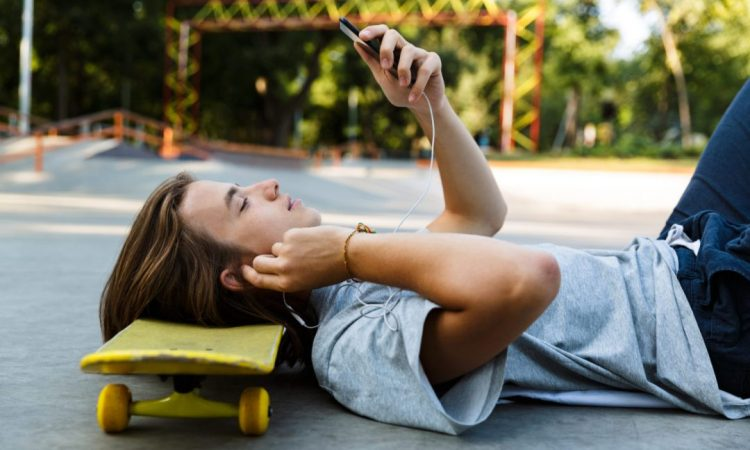 man lying on ground with head on skateboard looking at phone
