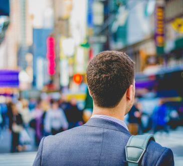 businessman walking outside in busy city