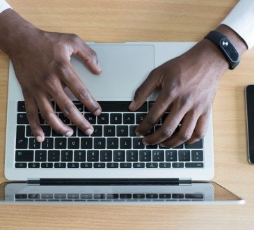 closeup of man's hands typing on laptop keyboard