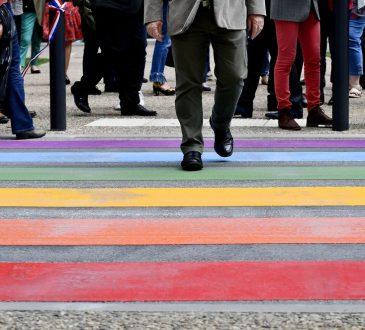 people walking across rainbow crosswalk