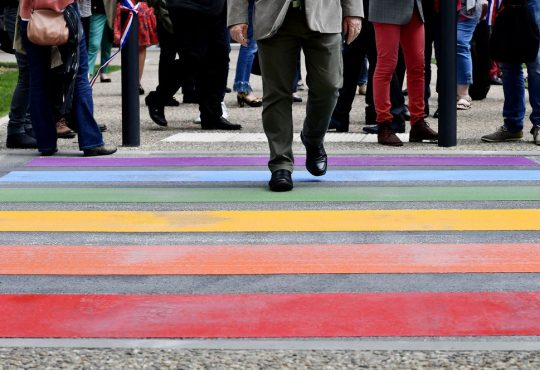 people walking across rainbow crosswalk