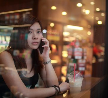 woman staring out window of cafe calling someone on cellphone