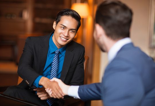 Closeup of two smiling business men shaking hands in cafe